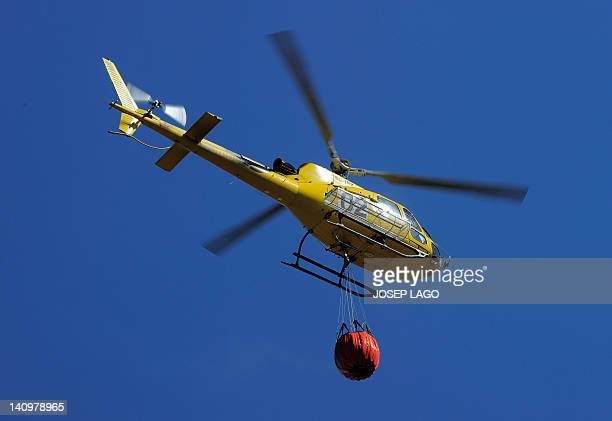 An helicopter collects water in a lake to help in bringing a fire under control in the northeastern region of Catalonia near the northern Spain...