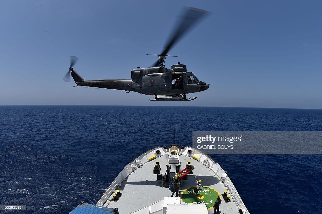 An helicopter from the Italian Marine evacuates a baby in emergency during a rescue operation with the Aquarius, a former North Atlantic fisheries protection ship now used by humanitarians SOS Mediterranee and Medecins Sans Frontieres (Doctors without Borders), on May 24, 2016 in the Mediterranean sea in front of the Libyan coast. / AFP / GABRIEL