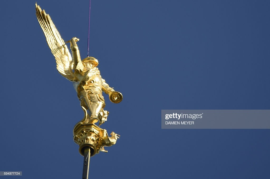 An helicopter lifts the statue of the Archangel Michael, regilded and restored with a new lighting rod, to replace it back atop the Mont Saint-Michel Abbey on May 26, 2016. / AFP / DAMIEN