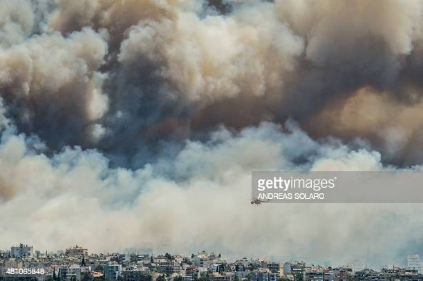 An helicopter of firefighters fly over smokes billowing over Athens on July 17 2015 as firemen were battling a brush fire in northeastern Athens and...