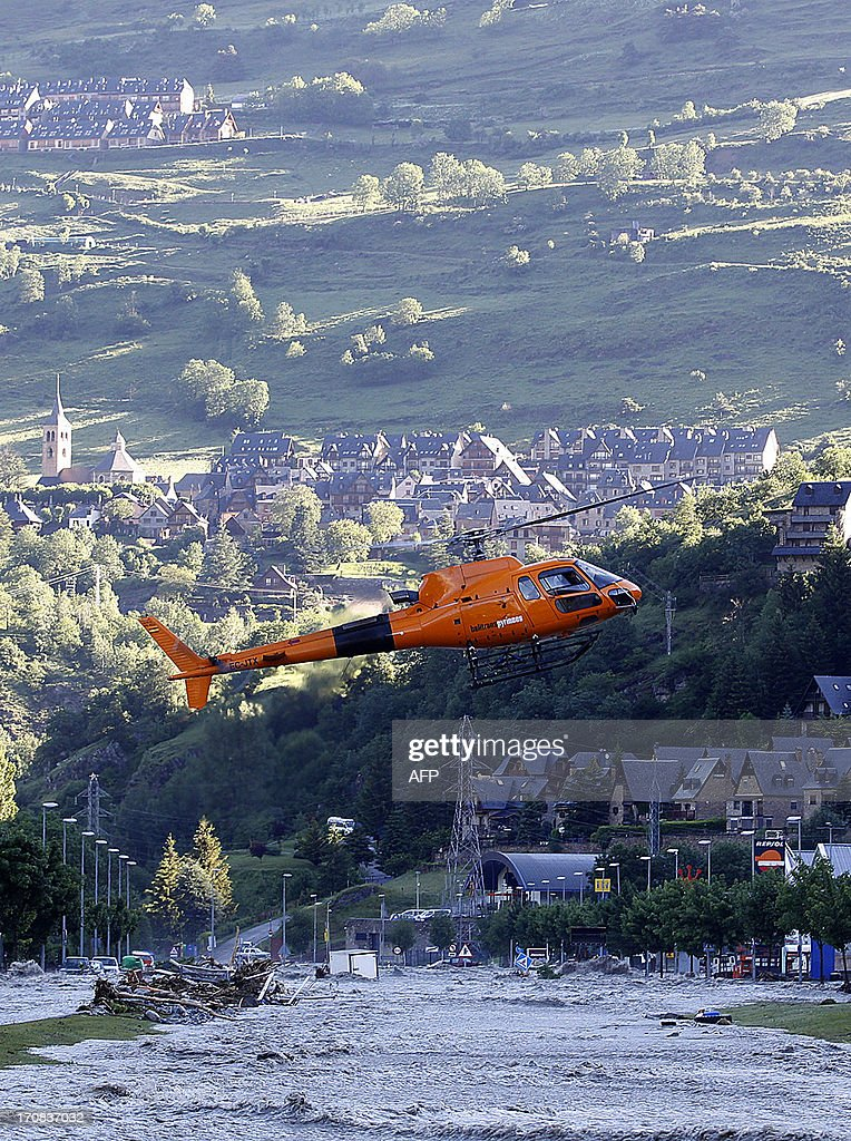 An helicopter of the electric company Endesa fies over the flooded bank of the Garona river in Vielha, northeastern Spain on June 19, 2013. Around 350 people were evacuated after heavy rains provoked floods in the north-east of Spain. AFP PHOTO/ QUIQUE GARCIA
