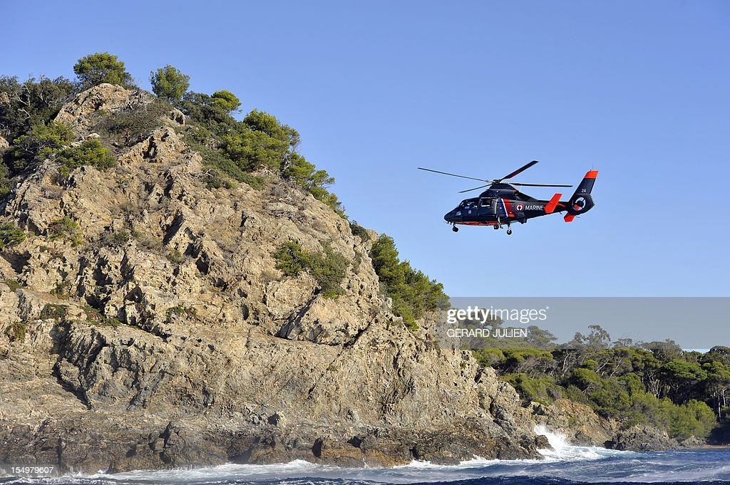 An helicopter of the French navy flies over the Porquerolles island, southeastern France on October 29, 2012 to search a 12-year-old British boy, who disappeared on October 27. Sixty soldiers and three civil security dog-handlers from Brignoles are paricipating in the search.