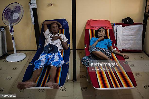 An HIV infected woman sits with her husband while getting an IV drip in the National League for Democracy's HIV clinic on November 29 2014 in Yangon...