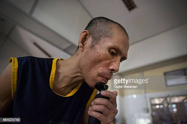 An HIV/AIDS patient shaves with an electric razor on February 21 2015 at Wat Phra Bat Nam Phu in Lop Buri Thailand Since beginning to care for...