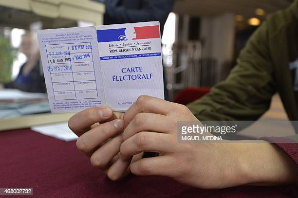 A an holds an electoral card during the second round of the French departemental elections in Bobigny outside Paris on March 29 2015 AFP PHOTO/MIGUEL...