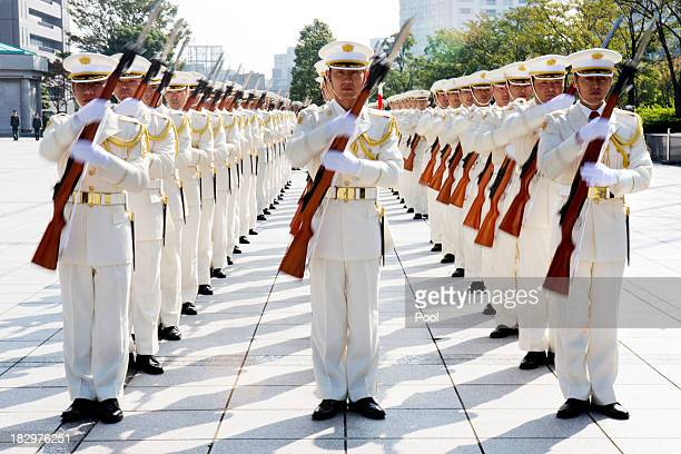 An honor cordon spin their rifles for Japanese Defense Minister Itsunori Onodera and US Secretary of Defense Chuck Hagel at the Ministry of Defense...