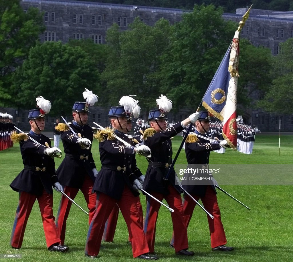 an honor guard carries the french flag as they lea pictures