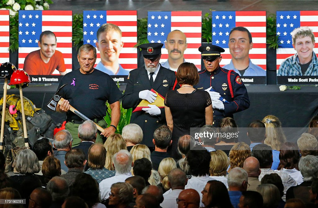 An honor guard presents families with an American Flag during a memorial service at Tim's Toyota Center July 9, 2013 in Prescott Valley, Arizona. The 19 firefighters, of the Granite Mountain Hotshots crew, died battling the fast-moving wildfire on June 30.