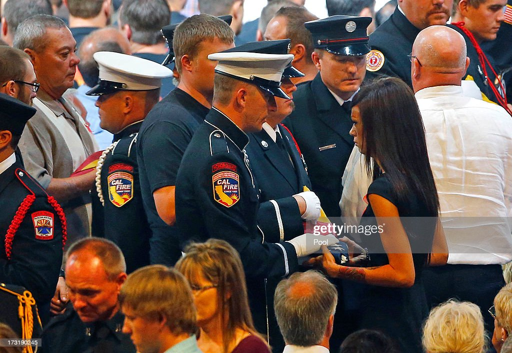 An honor guard presents Juliann Ashcraft, wife of fallen firefighter Andrew Ashcraft with an American Flag during a memorial service at Tim's Toyota Center July 9, 2013 in Prescott Valley, Arizona. The 19 firefighters, of the Granite Mountain Hotshots crew, died battling the fast-moving wildfire on June 30.