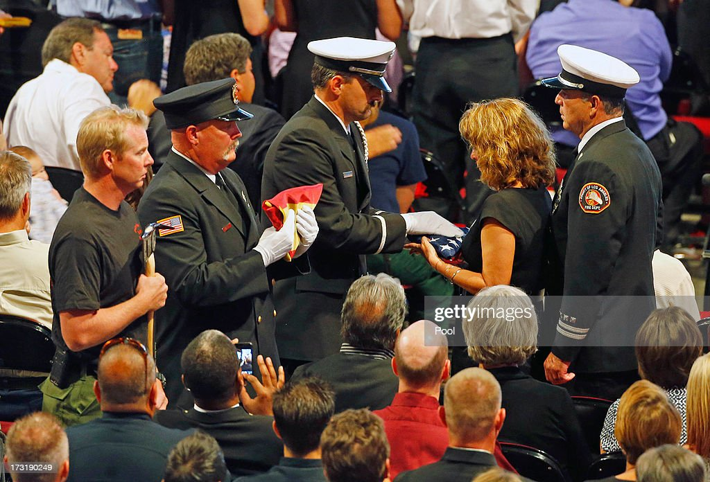 An honor guard presents LACo Fire Cap. Joe Woyjeck and his family. with an American Flag jonoring their son Kevin Woyjeck during a memorial service at Tim's Toyota Center July 9, 2013 in Prescott Valley, Arizona. The 19 firefighters, of the Granite Mountain Hotshots crew, died battling the fast-moving wildfire on June 30.