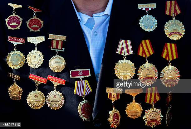 An honor guest with medals on his coat arrives to his seat to watch a military parade to commemorate the 70th anniversary of the end of World War II...