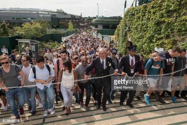 An Honorary steward guides tennis fans towards 'Murray Mound' ahead of day ten of the Wimbledon Lawn Tennis Championships at the All England Lawn...