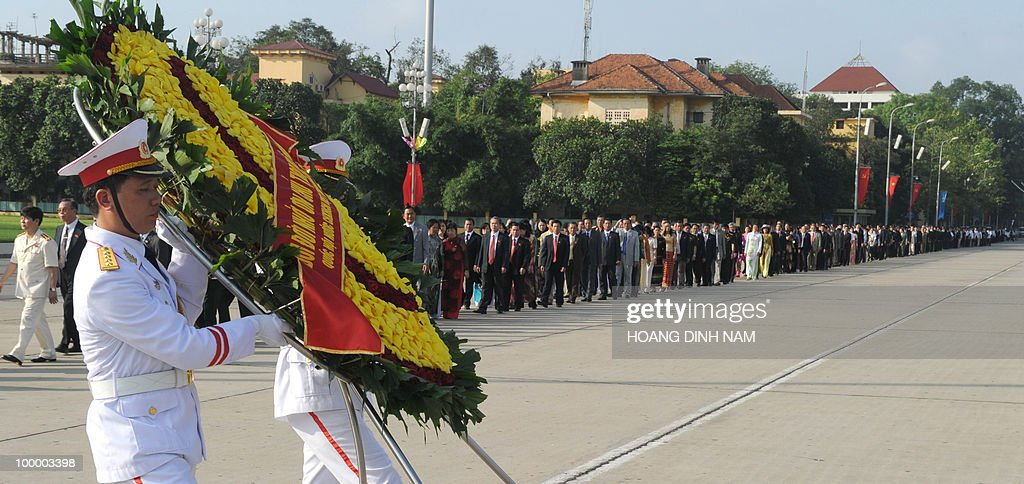 An honour guard carries a wreath as National Assembly delegates march toward the mausoleum of late president Ho Chi Minh to pay hommage to the founder of today's Vietnam prior to the opening of the National Assembly's summer session in Hanoi on May 20, 2010. Vietnam's communist-dominated legislature is to consider adopting a 'more humanitarian' method of executing criminals, at its month-long session, according to an official document. AFP PHOTO/HOANG DINH Nam