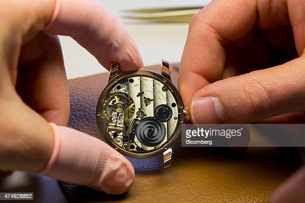 An horologist inspects the mechanism of a Benu Tourbillon luxury wristwatch at Moritz Grossmann GmbH watchmakers in Glasshuette Germany on Wednesday...