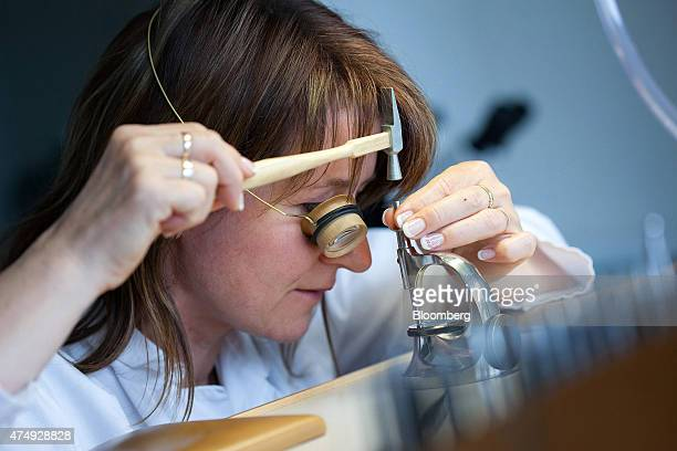 An horologist works on the mechanism of a wristwatch at Moritz Grossmann GmbH luxury watchmakers in Glasshuette Germany on Wednesday May 27 2015 The...