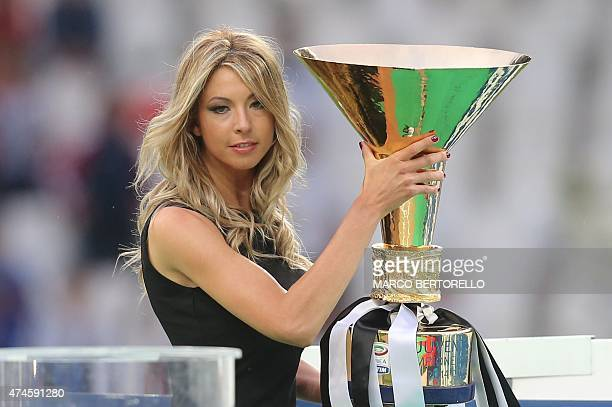 An hostess arrives with the Italian League's trophy before a victory ceremony following the Italian Serie A football match Juventus vs Napoli on May...