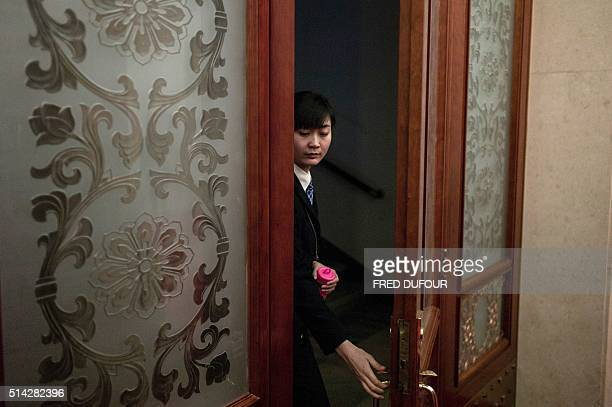 An hostess leaves a room during a meeting on Anhui province at the National People's Congress in the Great Hall of the People in Beijing on March 8...