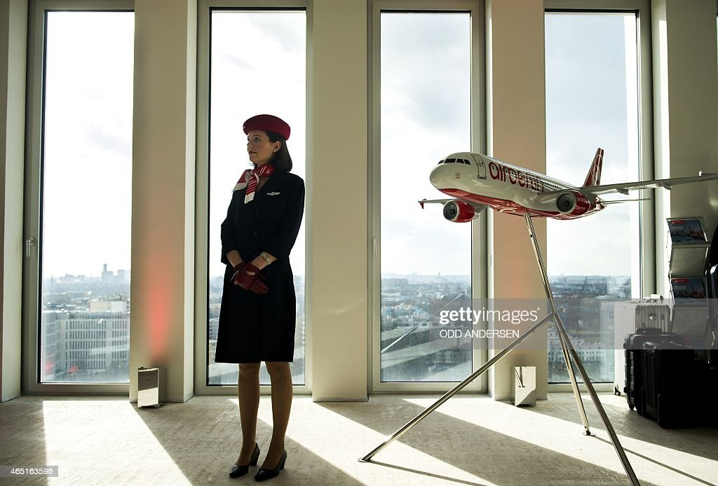 An hostess stands next to a model airplane of Germany's secondbiggest airline Air Berlin on the 16th floor of a building on March 3 2015 in Berlin...