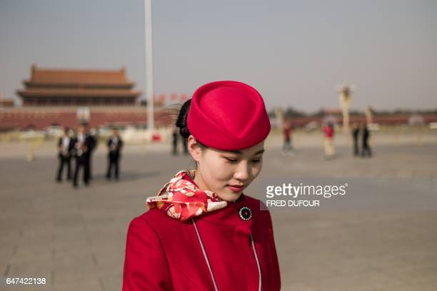 TOPSHOT An hostess walks in Tiananmen Square during the opening session of the Chinese People's Political Consultative Conference in the Great Hall...
