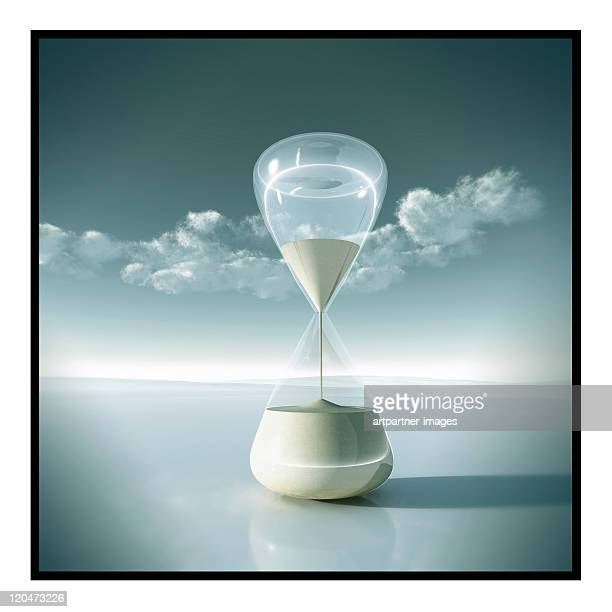 An hourglass in front of a clear sky with clouds