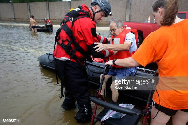 An HPD officer helps Frank Andrews into his walking chair after rescuing him from his flooded home in the Braeswood Place neighborhood Southwest of...