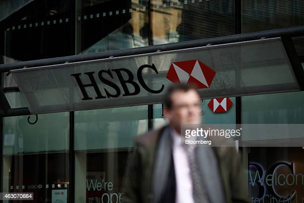 An HSBC logo sits on a sign above the entrance to a bank branch operated by HSBC Holdings Plc in London UK on Monday Feb 9 2015 The privatebanking...