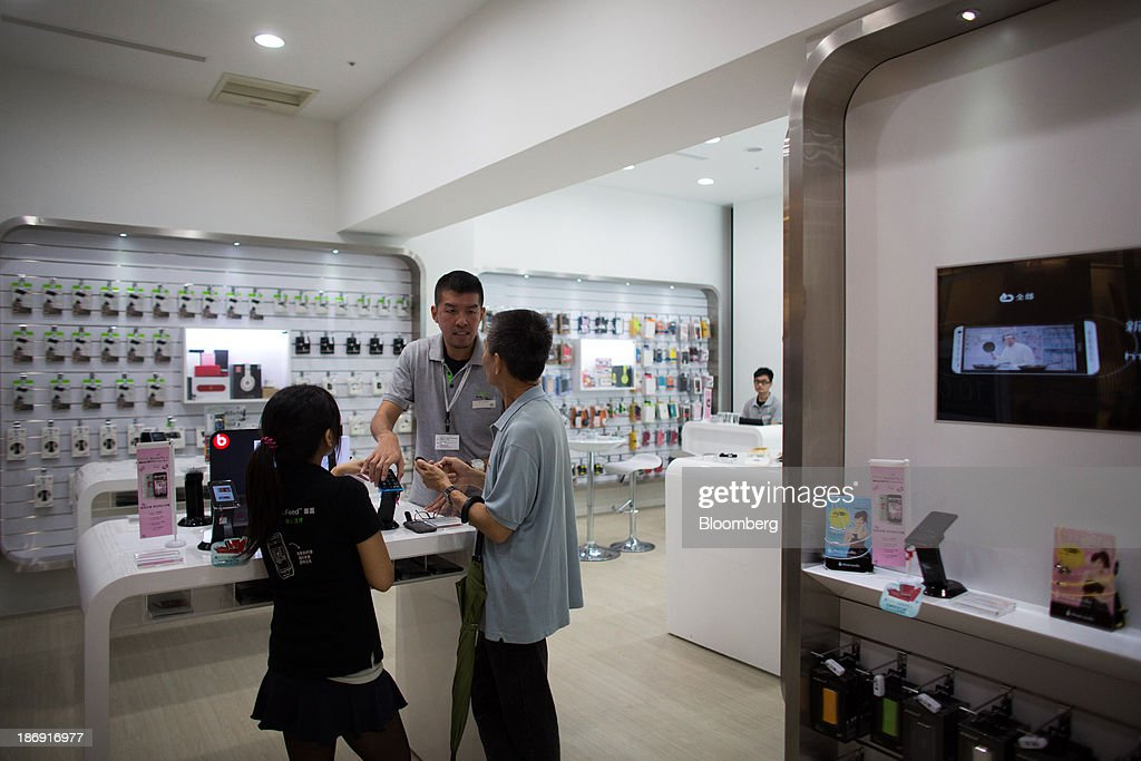 An HTC Corp. employee assists a customer at one of the company's stores in Taipei, Taiwan, on Monday, Nov. 4, 2013. Taiwans five-year bonds gained for the first time in four days, lowering the yield from a three-week high, after a report showed inflation cooled. The local dollar strengthened. Photographer: Lam Yik Fei/Bloomberg via Getty Images