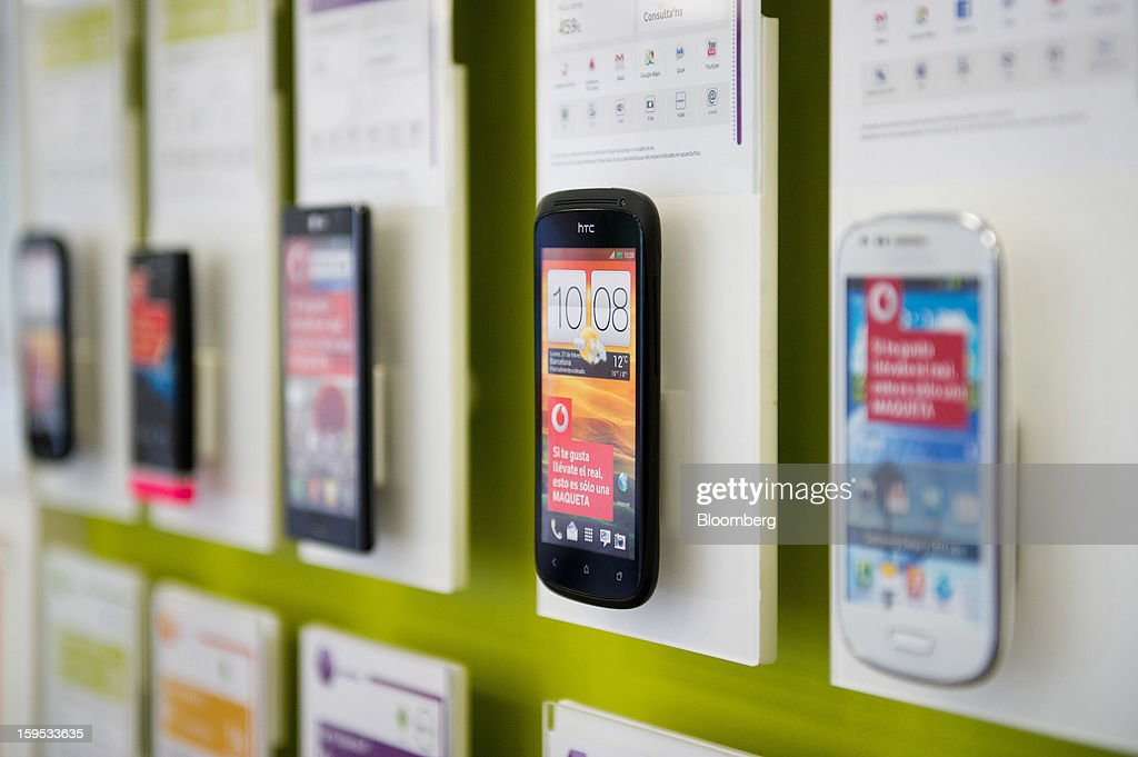 An HTC Corp. mobile handset sits on a display of smartphones inside a Vodafone Group Plc store in Barcelona, Spain, on Tuesday, Jan. 15, 2013. Vodafone Group Plc, the world's second largest mobile-phone company, plans to reduce the workforce at its Spanish unit as unemployment exceeding 25 percent in the recession-plagued country causes sales to drop. Photographer: David Ramos/Bloomberg via Getty Images