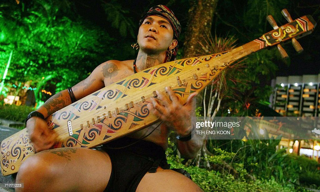An Iban musician plays his 'sape' a traditional musical instrument at the Waterfront one of the tourist spot in Kuching Sarawak the largest state in...