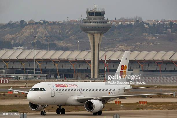 An Iberia plane passes near a control tower at Madrid Barajas Adolfo Suarez airport which is operated by group Aena on February 11 2015 in Madrid...