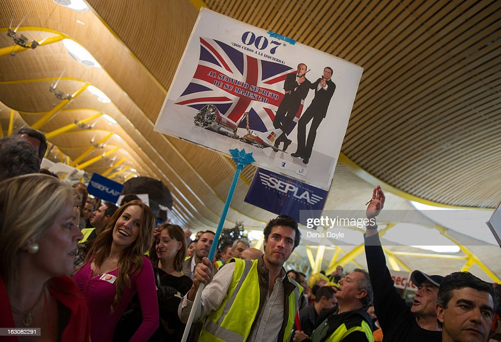 An Iberia worker holds a placard of representing Iberia chief executive Antonio Vazquez and chief executive officer Sanchez Lozano as fictional British secret agent James Bond during a protest at Barajas airport on March 4, 2013 in Madrid, Spain. Iberia workers have begun the second round of five day strikes in protest at plans by British based holding company IAG (International Consolidated Airlines Group), formed by the 2011 merger of Iberia and British Airways, to implement redundancies and pay cuts across the troubled Spanish airline. The strike is estimated to cause the cancelling of almost 1,300 flights this week, with a final round of five day strikes planned for March 18 to 22.
