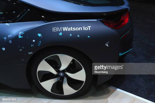 An IBM Watson IoT logo sits on the trunk of a Bayerische Motoren Werke AG i8 electric vehicle in the International Business Machines Corp pavilion at...
