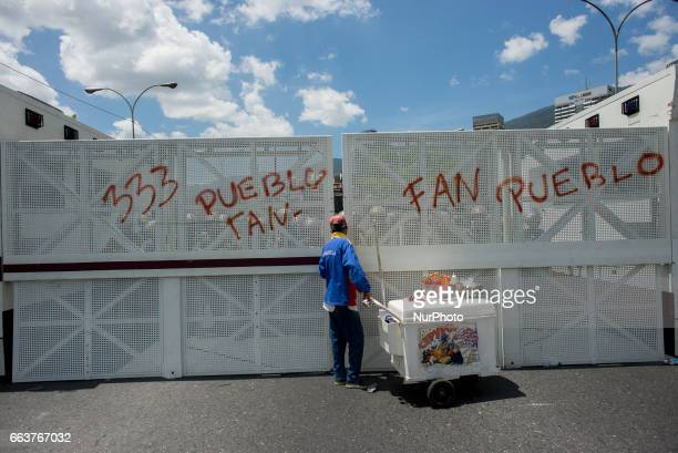 An ice cream street vendor walks in front of a fence set on the main highway of Caracas by the National Guard during a demonstration against the...