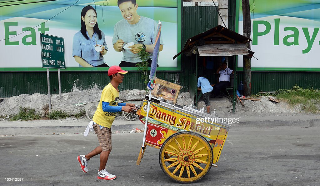 An ice cream vendor walks past an advertisement for a shopping mall under construction in Manila on January 31, 2013. The Philippines said on January 31 its economy grew by a better-than-expected 6.6 percent last year as confidence rose in President Benigno Aquino's efforts to fight corruption and alleviate poverty.