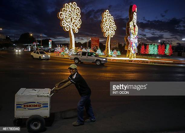 An ice cream vendor walks past Hugo Chavez's roundabout in Managua on January 17 2015 AFP PHOTO/ Inti OCON