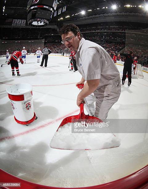 An ice crew member cleans the ice during a second period timeout during the game between the New Jersey Devils and the Montreal Canadiens at the...