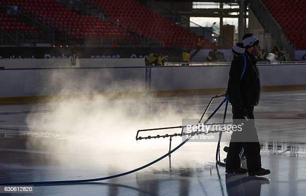 An ice crew worker sprays water on the ice during the build out of the outdoor rink for the 2017 Scotiabank NHL Centennial Classic between the...