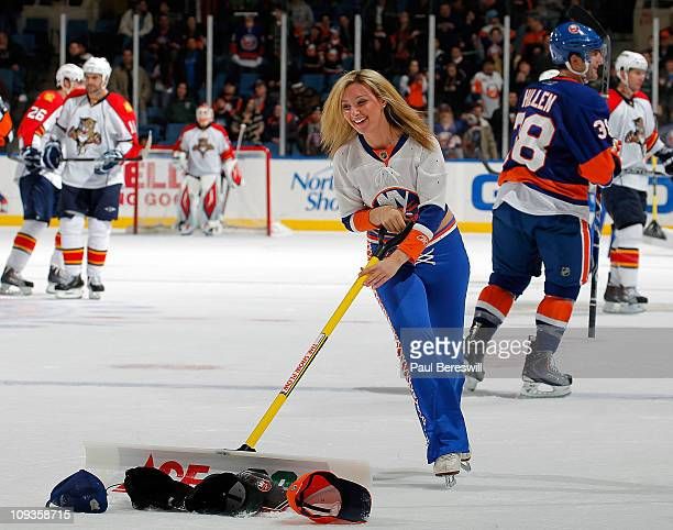 An Ice Girl clears hats off the ice after Matt Moulson of the New York Islanders scored his third goal of an NHL hockey game against the Florida...