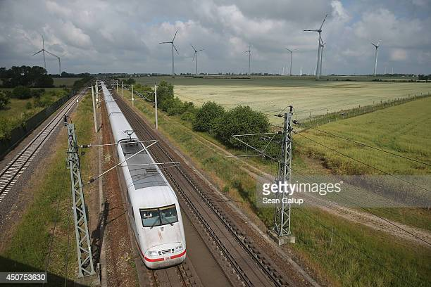 An ICE highspeed train operated by Deutsche Bahn passes by wind turbines on June 17 2014 near Wernitz Germany Deutsche Bahn is Germany's biggest rail...