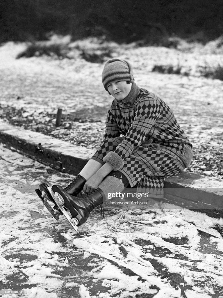 An ice skater adjusts her skates while on Connaught Water, a mile east of Chingford in the London Borough of Waltham Forest, London, England, mid 1930s.