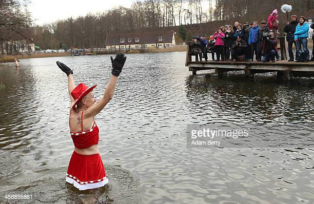 An ice swimmer waves to visitors in the Obersee in Lanke about 50 kilometers north of Berlin on December 22 2013 in Lanke Germany The swimmers who...