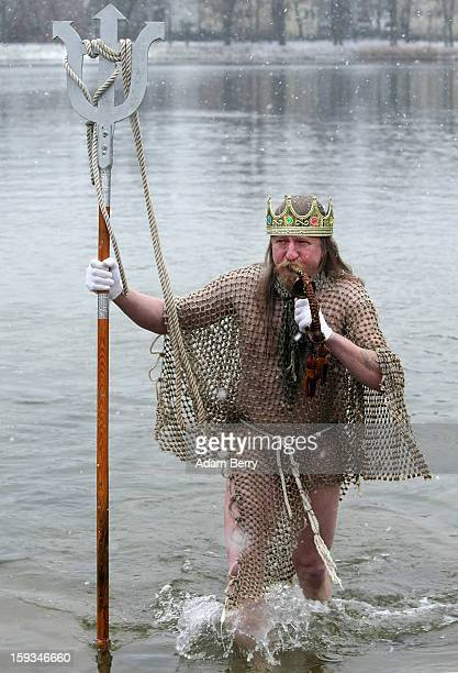 An ice swimming enthusiast dressed as Neptune leaves the cold waters of Orankesee lake during the 'Winter Swimming in Berlin' event on January 12...