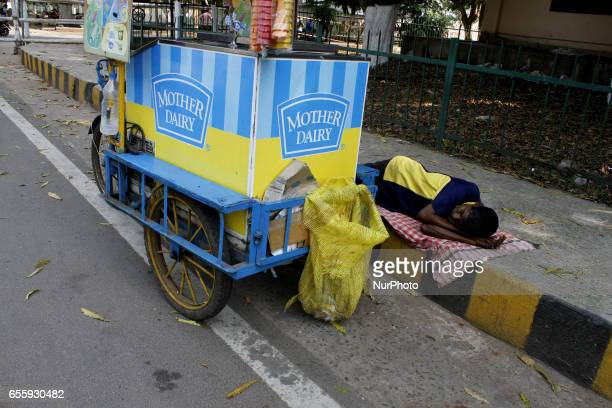 An icecream vendor sleeps on wayside as he takes a break from his business in a hot afternoon to beat the heat in Bhubaneswar on March 21 2017