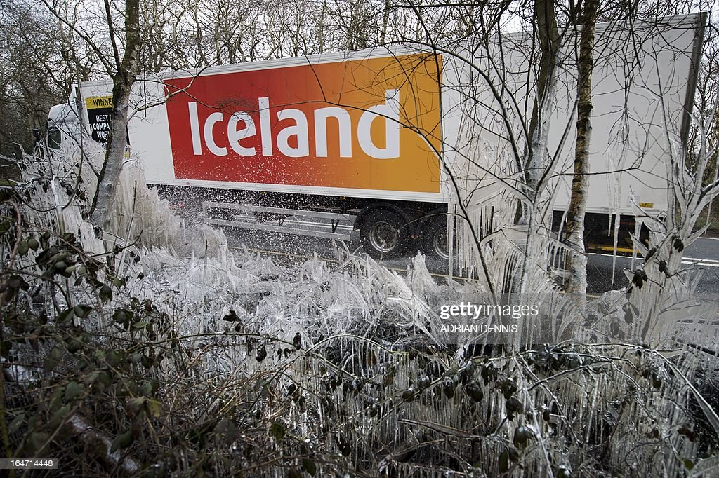 An Iceland supermarket lorry passes a section of icicles and ice-covered hedgerow caused by a water splashed from the roadside near Hazeley Bottom, south of Reading, on March 27, 2013. Britain is in the grip of what the media has dubbed 'Miserable March', an unseasonal cold snap that threatens to bring the UK a White Easter. AFP PHOTO / ADRIAN DENNIS