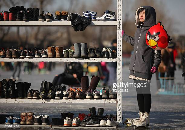 An iceskater holds an 'Angry Birds' balloon as she stands next to a shoe rack on a frozen lake in Beijing on January 2 2012 Skaters are a familiar...
