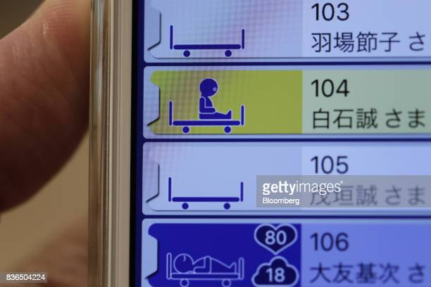 An icon showing a resident is seated up on a bed is displayed on the 'EGAO link' system on an Apple Inc iPhone in an arranged photograph at the As...