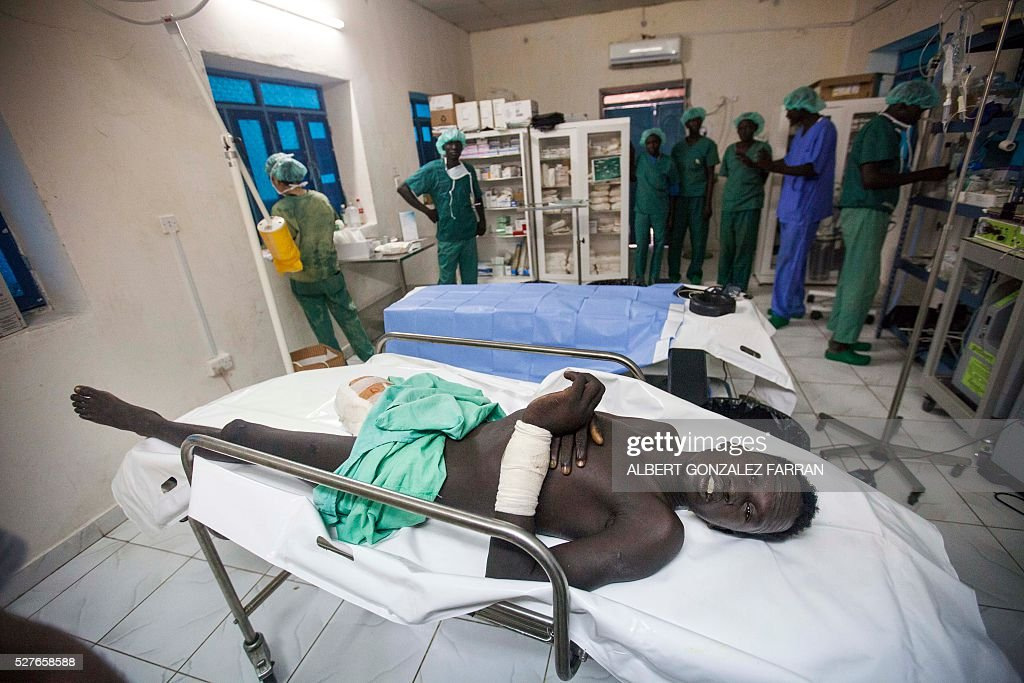 An ICRC medical team treats a patient with a recent amputation at the Maiwut hospital, on May 3, 2016, after he was shot during an attack by armed men when he was riding his cattle in the Unity county. More than three dozen victims of violence have sought assistance at an International Committee of the Red Cross (ICRC)-supported hospital in Maiwut. The health facility is now providing medical and surgical care to the wounded of recent attacks near Gambella, Ethiopia, where nearly 200 people were killed and more than 100 children abducted.Many of the 39 men, women and children admitted to the hospital are suffering from gunshot injuries as a result of the mid-April clashes along the Ethiopian border.Maiwut hospital is located in the Upper Nile region about 20 kilometers from Gambella. It is the only medical facility in the region providing surgical and advanced health care to the nearly 80,000 people living there.The ICRC currently supports seven medical and primary health care facilities in South Sudan. Since January this year our teams have performed more than 1,600 surgeries. / AFP / Albert Gonzalez Farran
