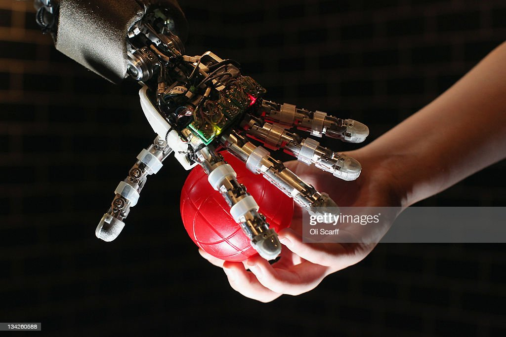 An iCub robot built by the Italian Institute of Technology tracks and grabs a red ball in the Robotville exhibition at the Science Museum on November 29, 2011 in London, England. The Science Museum's Robotville exhibition showcases 20 unique and cutting-edge robots from European research laboratories, it is free to enter and runs from December 1-4, 2011.