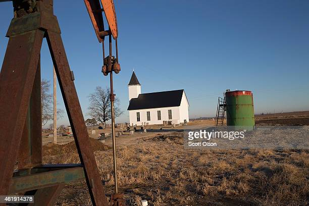 An idled pump jack once used to extract crude oil from the ground and a tank battery used to temporarily store the freshlypumped crude sit near the...