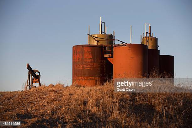 An idled pump jack once used to extract crude oil from the ground and a tank battery used to temporarily store the freshlypumped crude rust away in a...
